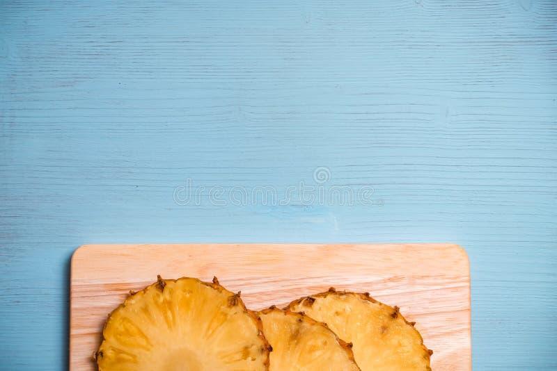 Зрелые части ананаса на борту и голубой деревянный стол стоковое изображение rf