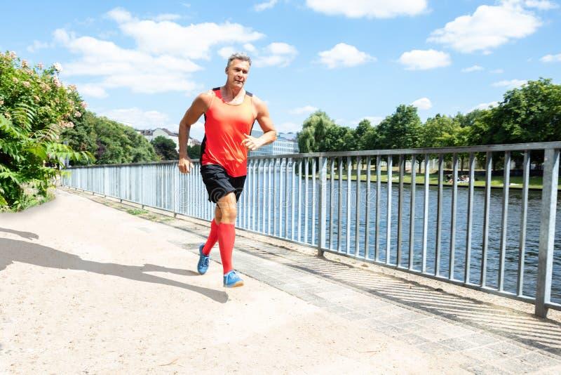 Зрелый атлетический человек бежать на тротуаре стоковая фотография rf
