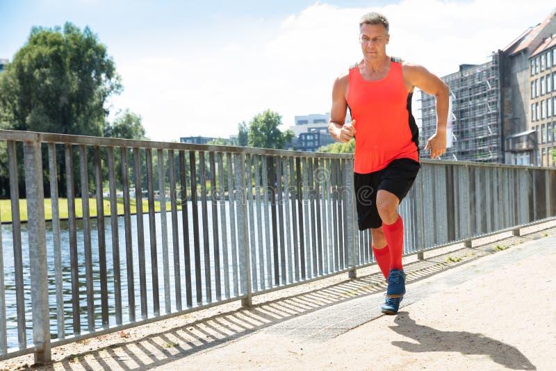 Зрелый атлетический человек бежать на тротуаре стоковая фотография