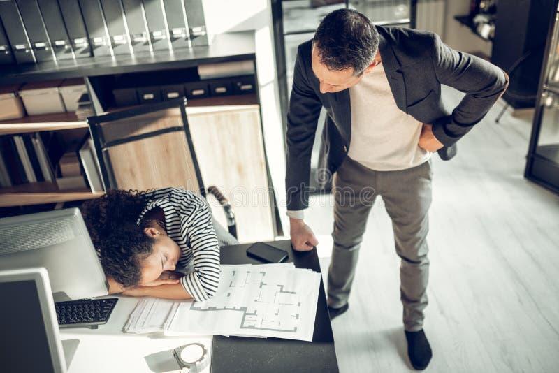 Зрелый бизнесмен крича на секретарше спать на таблице стоковое изображение rf