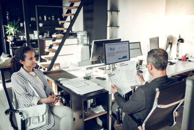 Зрелый бизнесмен читая CV женщины сидя около его стоковое фото rf