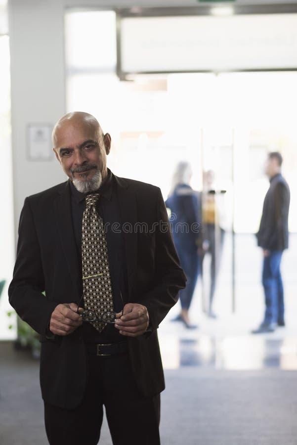 Зрелый босс в офисе представляя и смотря камеру с людьми в окнах предпосылки стоковое изображение rf