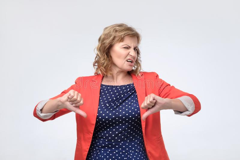 Зрелый давать женщины отрицательные большие пальцы руки вниз с жеста неутверждения стоковое фото