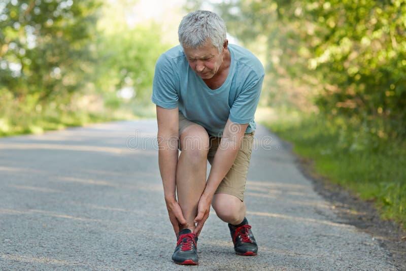 Зрелый мужчина вытянул его ногу во время внешней тренировки, страдает от ужасной боли, представляет снаружи Раздражанный пенсионе стоковые изображения rf