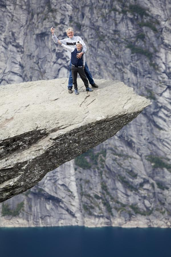 Зрелый отец с положением сын-подростка на скале Trolltunga совместно Развевать их руки и усмехаться стоковое фото rf