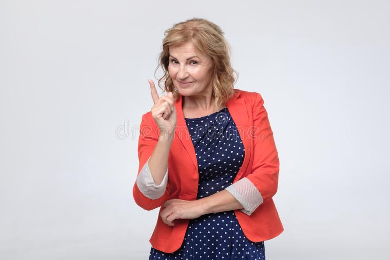 Зрелый палец пунктов женщины на вас с уверенным выражением стоковые изображения