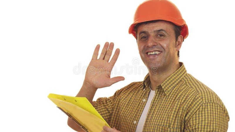 Зрелый построитель мастера в защитном шлеме делая примечания на доске сзажимом для бумаги стоковые изображения rf