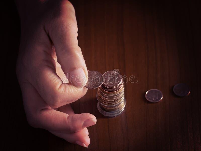 Зрелый, рука женщины кладя монетки в кучу, кучу, на белую предпосылку скатерти конец Европейские монетки евро, подсчитывая стоковое изображение