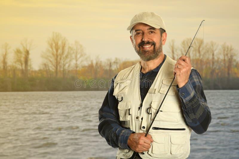 Зрелый рыболов озером стоковое фото
