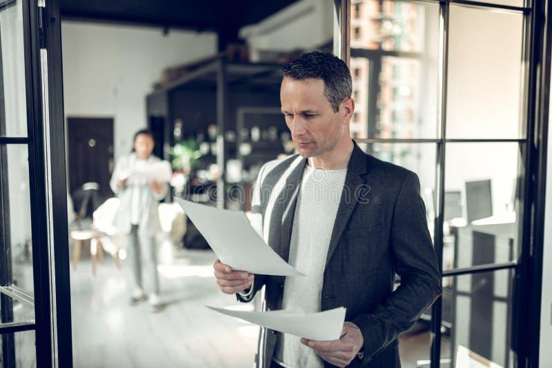 Зрелый серьезный бизнесмен читая некоторые отчет и документы стоковые фото