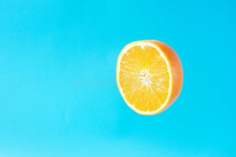 Зрелый сочный уменьшанный вдвое Levitating апельсина плавая в воздухе на свете - голубой предпосылке Vegan вытрезвителя лета здор стоковые изображения rf