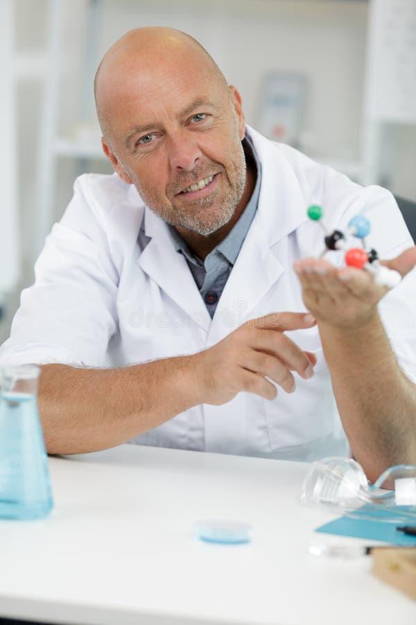 Зрелый ученый делая исследование над структурой молекулы ДНК стоковые изображения