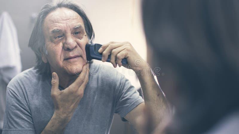 Зрелый человек брея перед зеркалом стоковое изображение