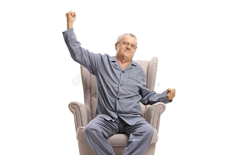 Зрелый человек в pyjamas сидя в кресле и протягивать стоковые изображения