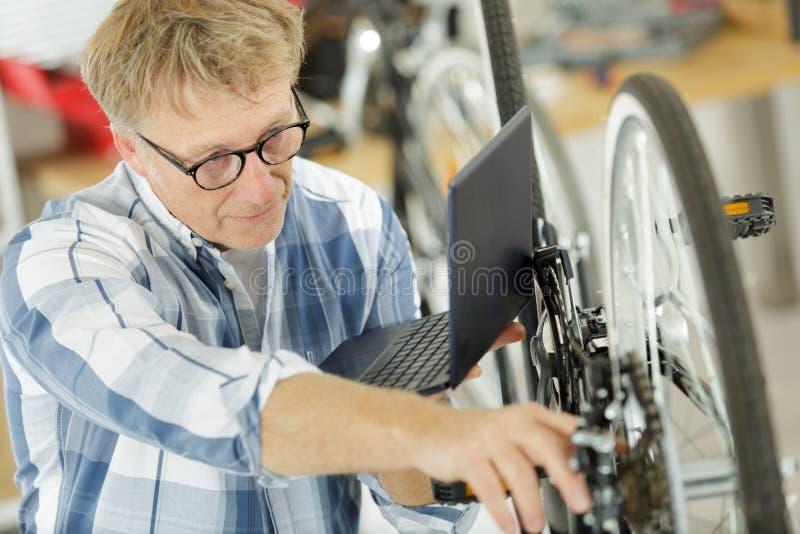 Зрелый человек используя ноутбук для ремонтировать велосипед дома стоковые изображения