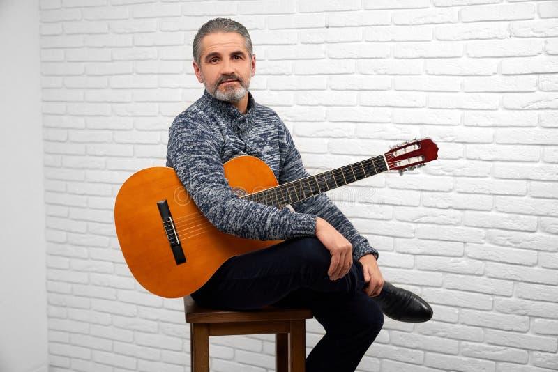 Зрелый человек представляя в студии с гитарой стоковое изображение rf