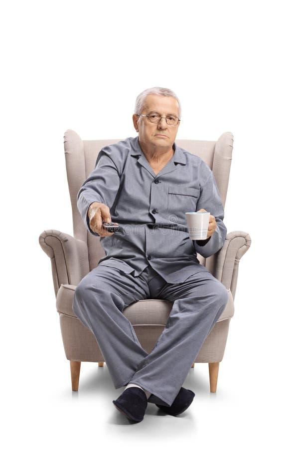 Зрелый человек при дистанционное управление и чашка сидя в armchai стоковое фото rf