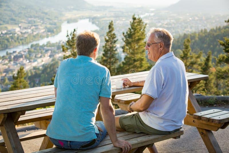 2 зрелых люд сидя на деревянном столе на смотровой площадке поверх горы стоковое изображение
