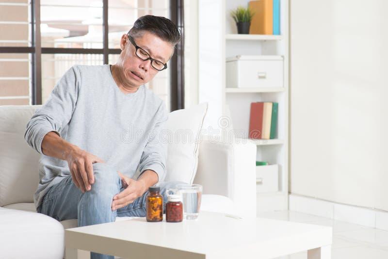 Зрелая азиатская боль колена человека стоковые фотографии rf