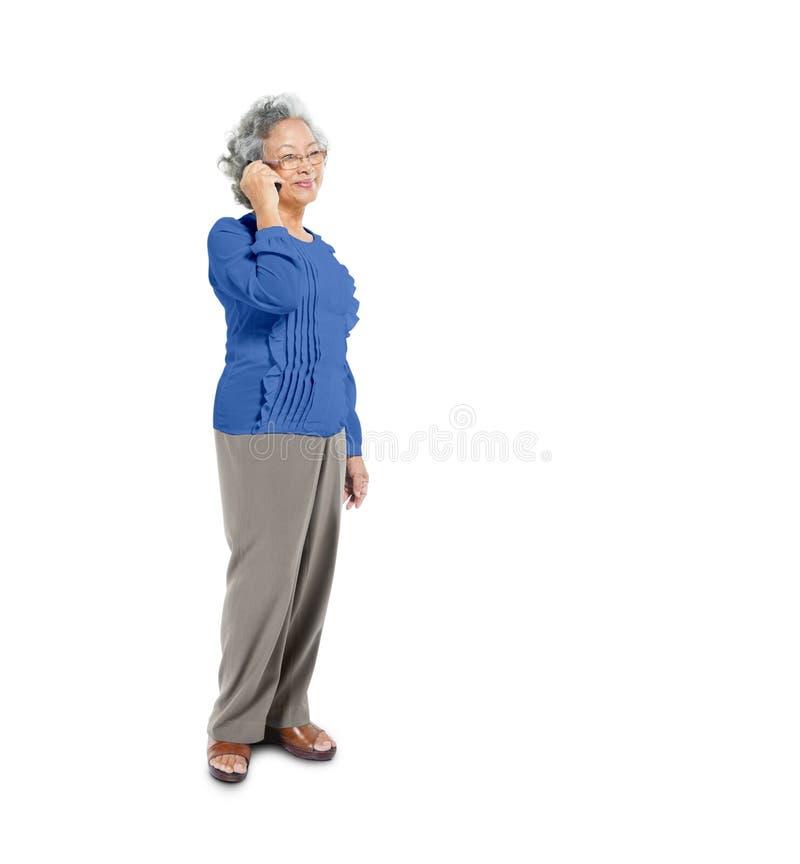 Зрелая азиатская женщина используя ее мобильный телефон стоковые фотографии rf