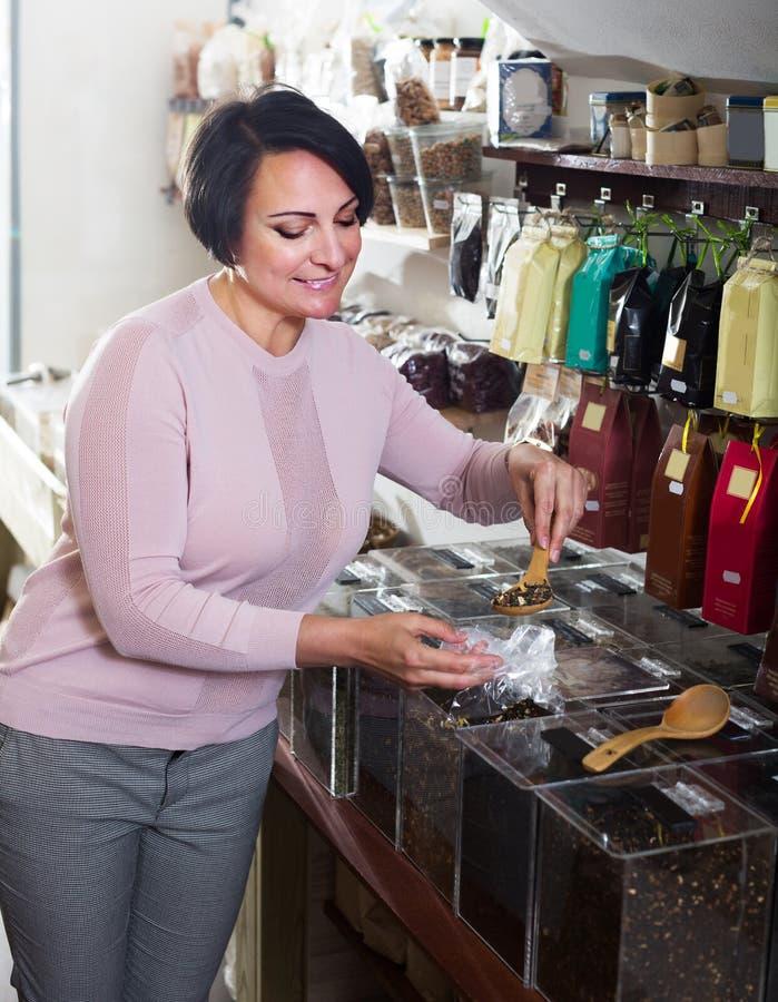 Зрелая женщина брюнет выбирая чай стоковое изображение