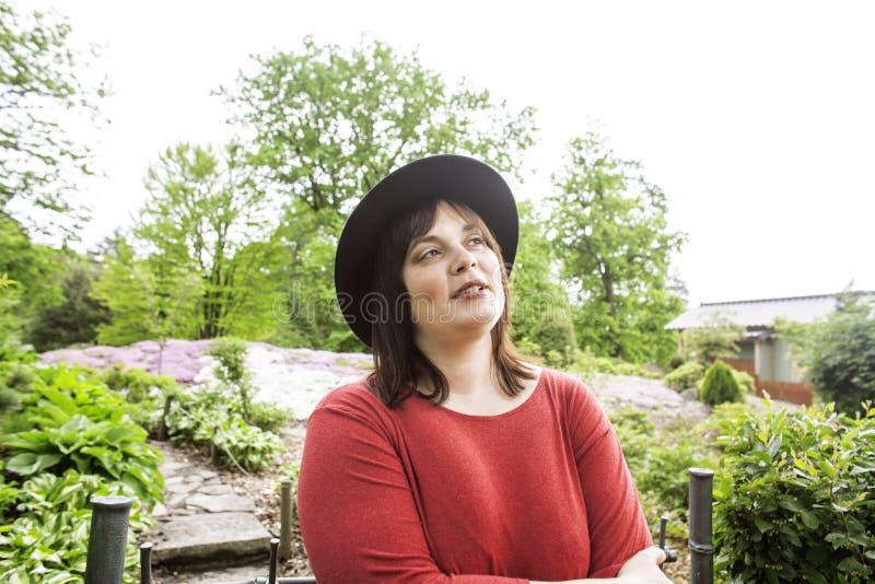 Зрелая женщина брюнет в шляпе зеленого сада нося, усмехающся, дружелюбный welkoming, конец концепции людей образа жизни вверх стоковое фото rf