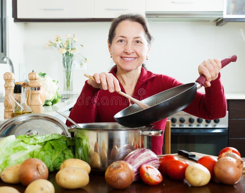Зрелая женщина варя обед с skillet стоковые фото