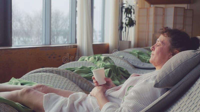 Зрелая женщина в постаретый носит белый халат в центре курорта лежа на чае пить софы и смотрит в окне с стоковое изображение rf