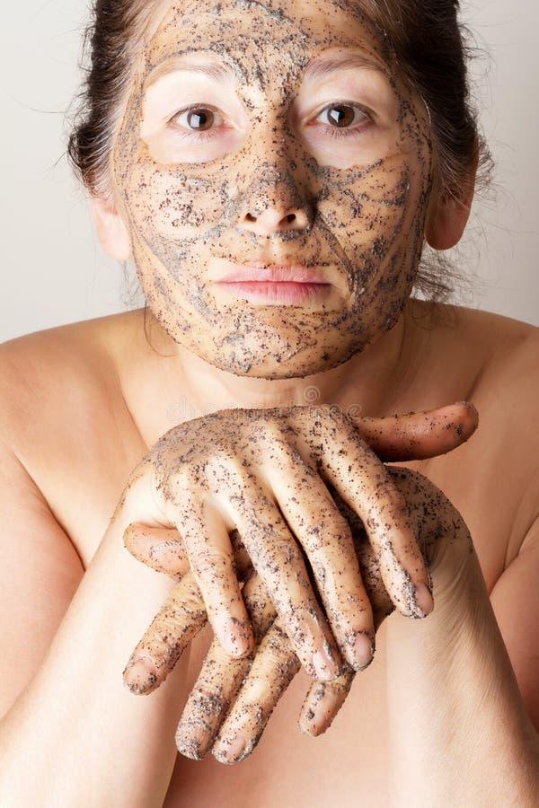 Зрелая женщина делая косметическую маску стоковое фото rf