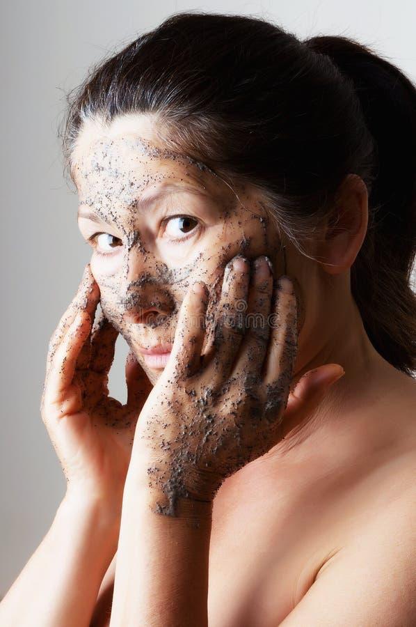 Зрелая женщина делая косметическую маску стоковая фотография rf