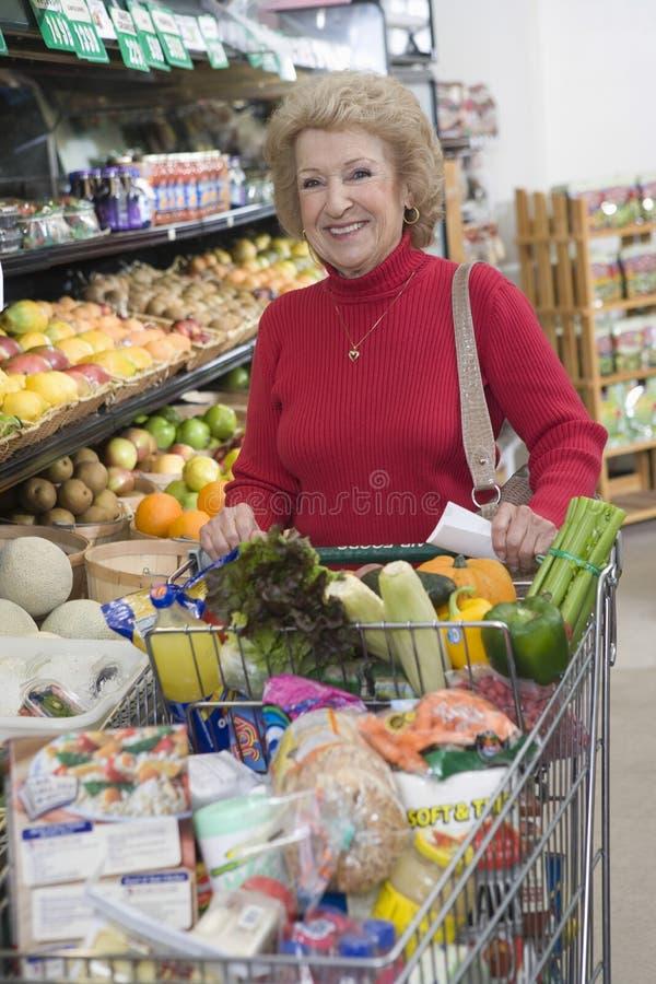Зрелая женщина делая посещение магазина бакалеи стоковая фотография