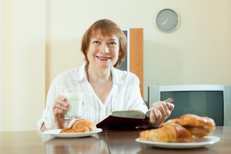Зрелая женщина имея завтрак с молоком стоковые фотографии rf