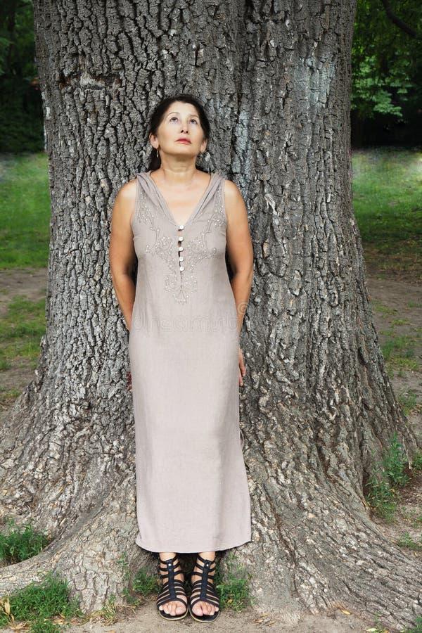 Зрелая женщина около дерева в парке стоковая фотография rf
