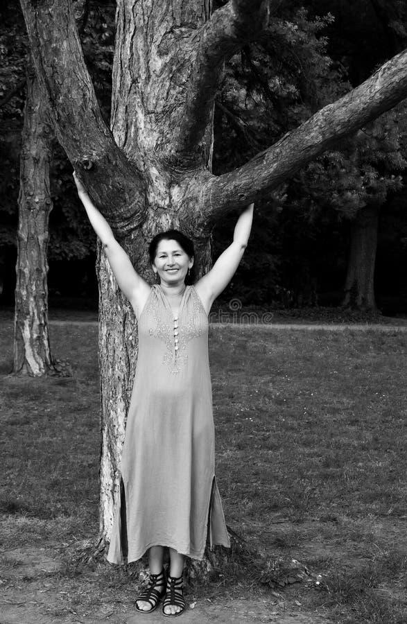 Зрелая женщина около дерева в парке стоковые изображения