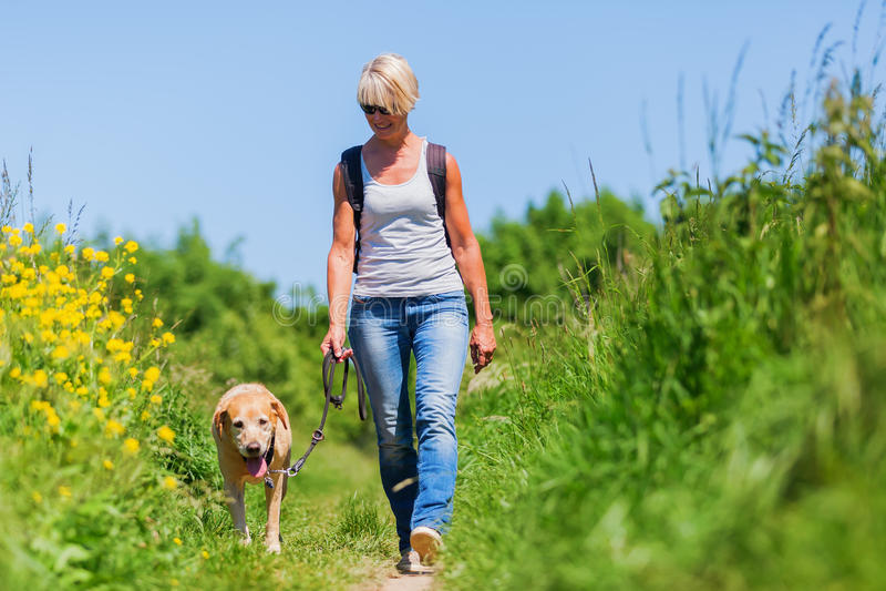Зрелая женщина при собака принимая пеший туризм в стране стоковая фотография rf