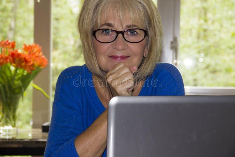 Зрелая женщина работая на портативном компьютере стоковое изображение rf
