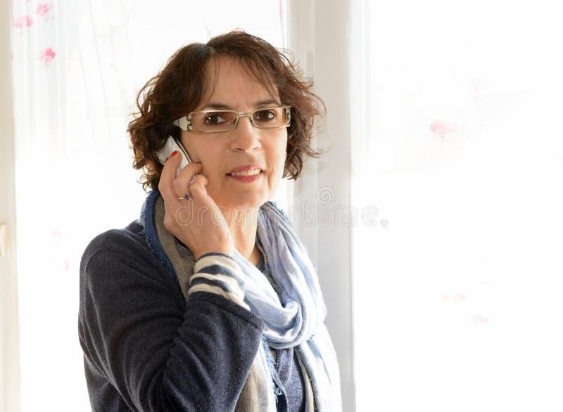 Зрелая женщина с мобильным телефоном стоковая фотография