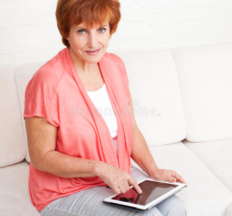 Зрелая женщина с ПК таблетки стоковые изображения