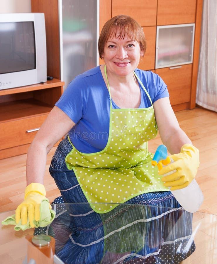 Зрелая женщина трет пыль стоковое изображение rf