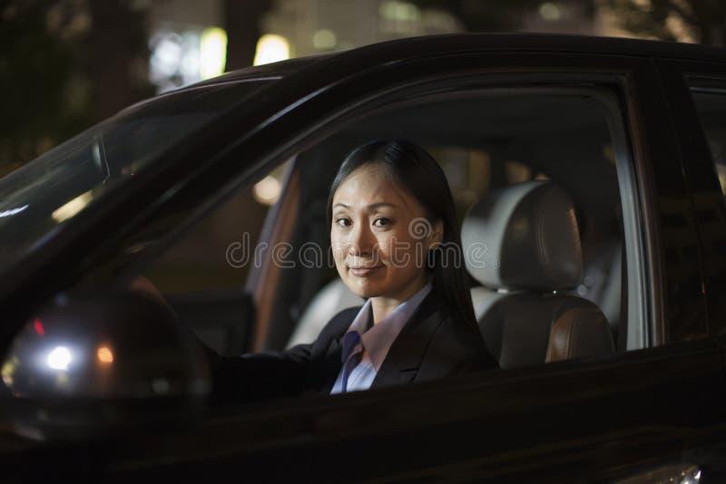 Зрелая коммерсантка управляя автомобилем стоковые фото