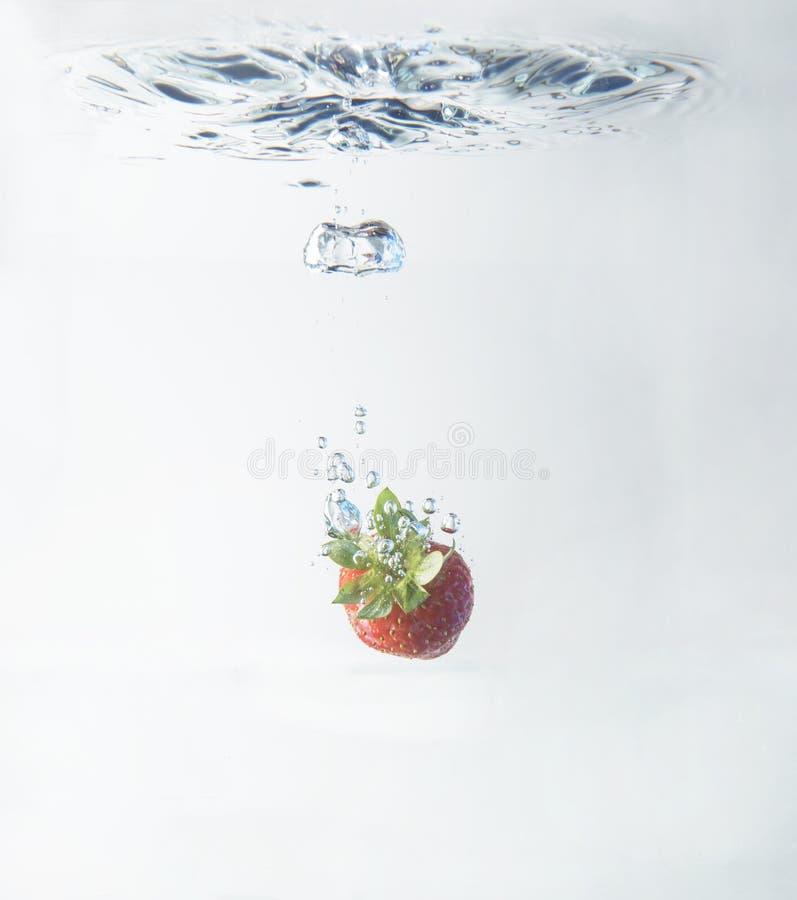 Зрелая клубника будучи паданным в бассейн воды стоковое фото rf