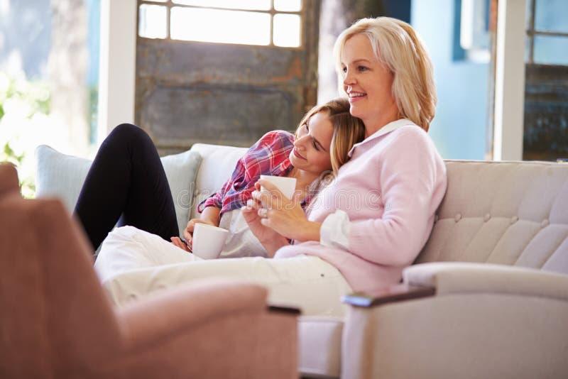 Зрелая мать при взрослая дочь смотря ТВ дома стоковая фотография rf