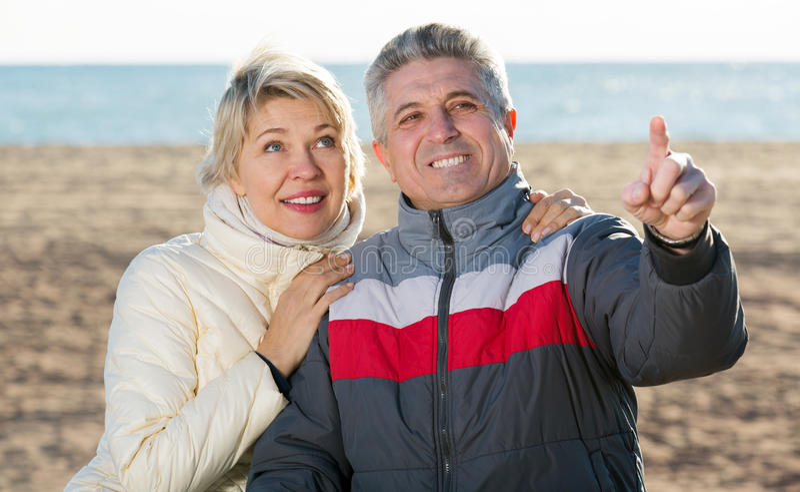 Зрелая пара идет outdoors и пункт вручную стоковое фото rf