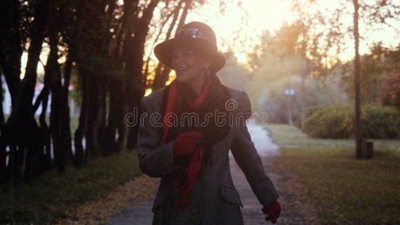 Зрелая элегантная счастливая женщина во времени носит в танцах пальто и шляпы в парке внешнем стоковые фото