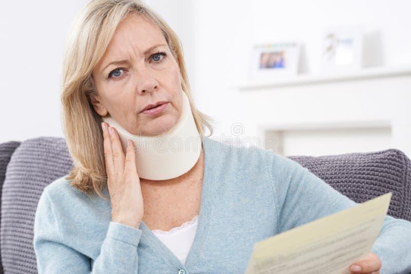 Зрелое письмо чтения женщины после получать ушиб шеи стоковые изображения