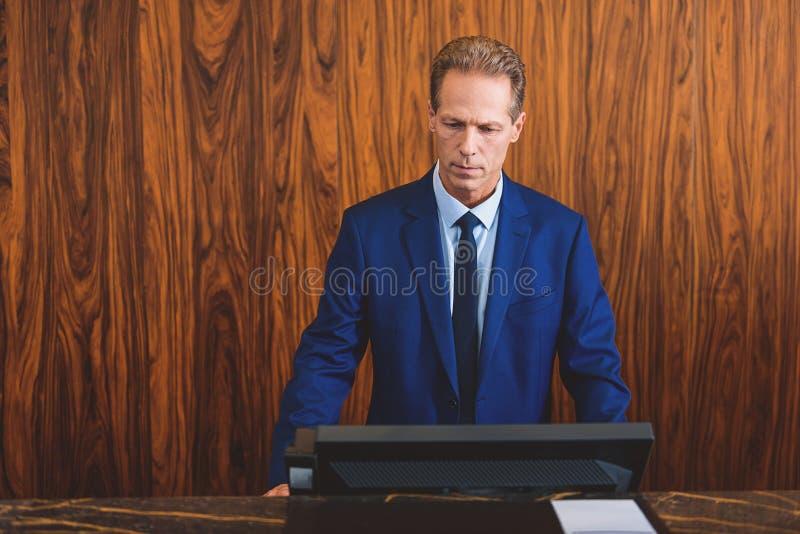 Зрелое хозяин гостиницы стоя на приеме стоковые изображения