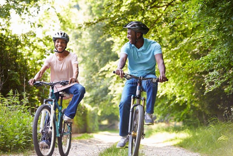 Зрелые Афро-американские пары на езде цикла в сельской местности стоковое изображение