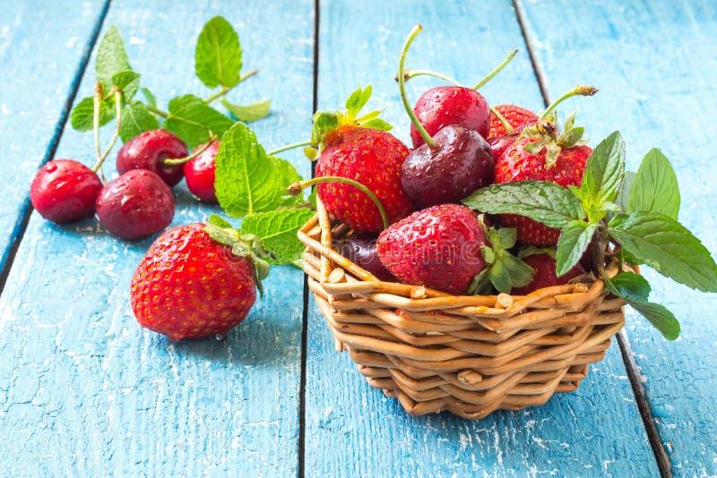 Зрелые клубники и вишни в корзине стоковые фотографии rf