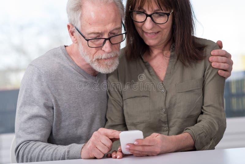 Зрелые пары используя мобильный телефон стоковая фотография