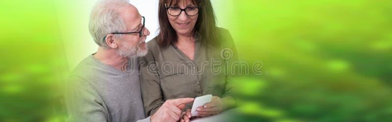 Зрелые пары используя мобильный телефон стоковое фото